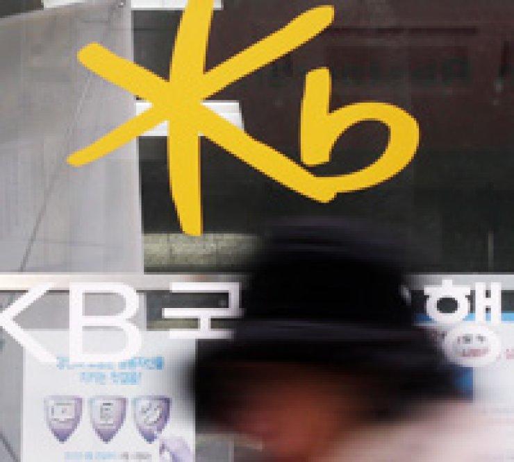 A person walks past a KB Kookmin Bank branch in Seoul, Monday. / Yonhap