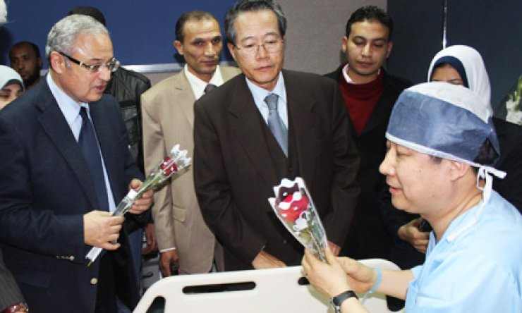 Egyptian tourism minister Hesham Zazoua, left, and Korean ambassador in Cairo, center, visit a Korean tourist who was injured during an explosion that targeted a tourist bus in Egypt, late Sunday. / AP-Yonhap