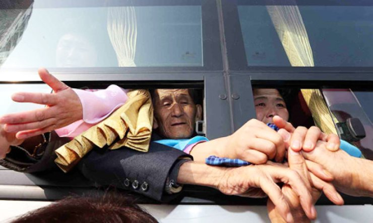 Family members attempt to hold on to each others' hands as North Koreans board the bus to part from their South Korean relatives after holding their final reunions at Mt. Geumgang in North Korea's east coast, Tuesday./ Yonhap