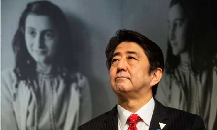 Japan's Prime Minister Shinzo Abe looks at pictures of Anne Frank as he visits the Anne Frank House museum in Amsterdam, the Netherlands, Sunday. / AP-Yonhap