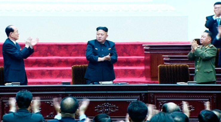 North Korean leader Kim Jong-un, center, Kim Yong-nam, left, president of the Presidium of the Supreme People's Assembly (SPA) and Choe Ryong-hae, the North Korean military's top political officer, applaud after Kim Jong-un was re-elected as the first chairman of the National Defense Commission, Wednesday, during an SPA session held in Pyongyang. This picture was captured from North Korea's national broadcaster KRT. / Yonhap