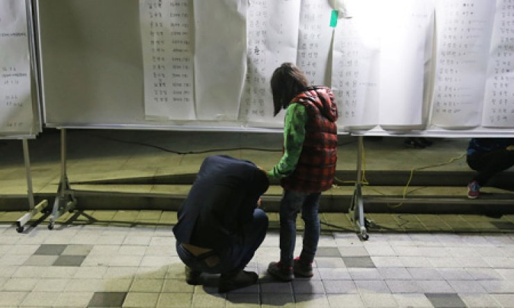 A family member of a missing person from the sinking of the ferry Sewol cries after checking the list of those rescued at a gym on Jindo Island, South Jeolla Province, Wednesday. The sinking of the passenger ship in waters off the country's southern coast has left about 280 people missing and nine dead as of Thursday. / Yonhap
