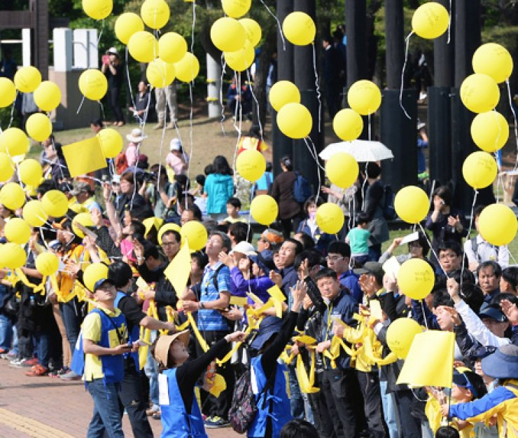 Visitors to the joint memorial altar for ferry-sinking victims in Ansan, Gyeonggi Province, Sunday, fly yellow balloons during an event to commemorate them. / Korea Times
