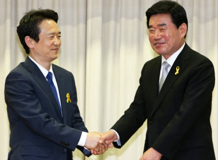 Reps. Nam Gyeong-pil, left, of the ruling Saenuri Party, and Kim Jin-pyo of the main opposition New Politics Alliance for Democracy, shake hands ahead of their debate at the Gyeonggi Provincial Assembly in Suwon, Monday. The two are competing for the Gyeonggi Province governor post in the upcoming June 4 local elections. / Yonhap