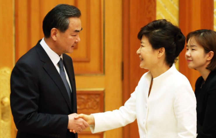 President Park Geun-hye, right, shakes hands with Chinese Foreign Minister Wang Yi at Cheong Wa Dae, Seoul, Monday. / Yonhap