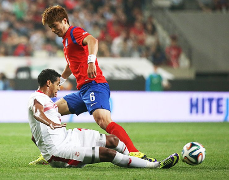 Midfielder Ki Sung-yueng, right, fights for control of the ball with Tunisia's striker Isaam Jemaa during a friendly at Seoul World Cup Stadium in Mapo, Wednesday. / Yonhap