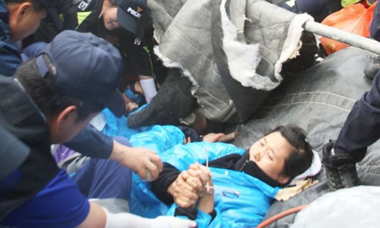 Police officers pull protesters out of a hole on a mountain in Miryang, South Gyeongsang Province, Wednesday. Police removed sit-in camps for residents who have been protesting against a power transmission tower project for years. / Yonhap