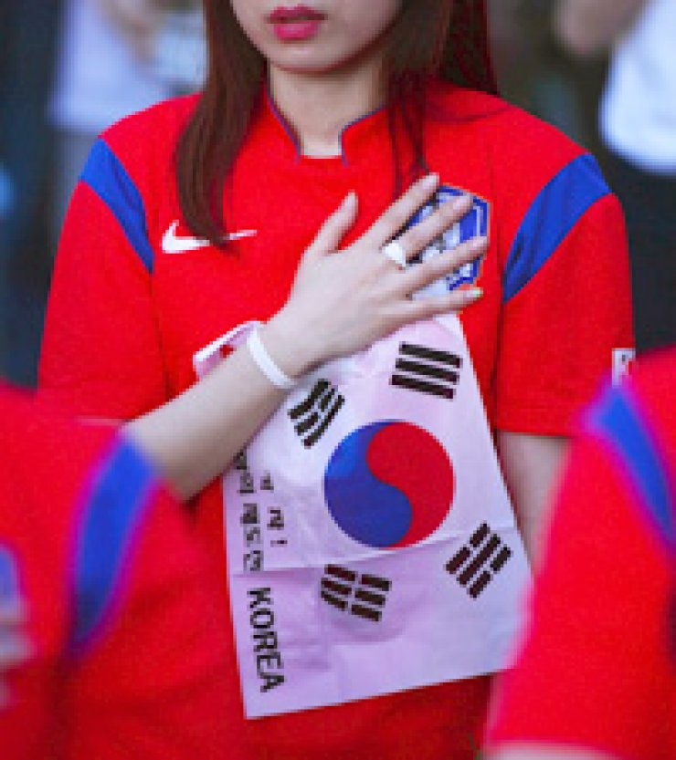 A female football fan salutes during a street cheering event at Gwanghwamun Square, central Seoul, on June 27, prior to the match between Korea and Belgium.