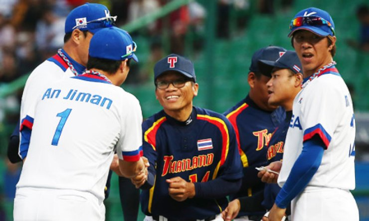 Baseball players from South Korea and Thailand greet each other before their game at the Incheon Asian Games at Munhak Baseball Stadium, Monday. / Yonhap