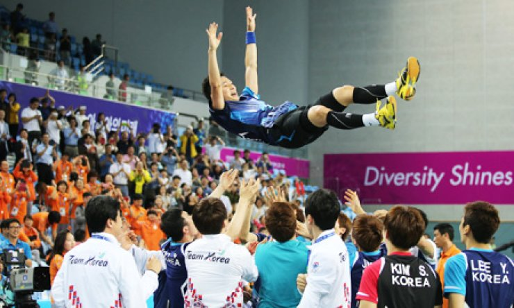South Korea badminton players and coaches toss Lee Hyun-il into the air at the Gyeyang Gymnasium in Incheon, Tuesday, after he clinched a 2-0 victory against China's Gao Huan in the fifth match and led his team to win the gold in the team event. / Yonhap