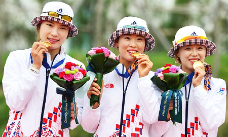 South Korean female archers, from left, Jung Dasomi, Lee Tuk-young and Chang Hye-jin, pose after winning gold medals in the women's team recurve archery final after defeating their Chinese opponents 3-0 at the Gyeyang Asiad Archery Field in Incheon, Sunday. / Korea Times photo by Shim Hyun-chul