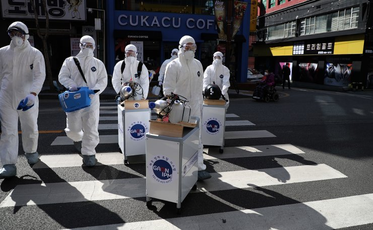 Workers wearing protective gears spray disinfectant as a precaution against the coronavirus at a shopping street in Seoul, South Korea, Thursday, Feb. 27, 2020. Korea Times photo by Choi Won-suk