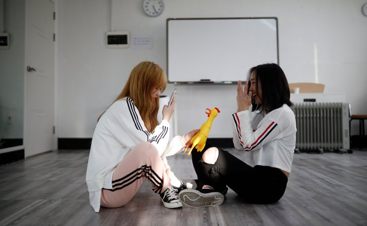 Japanese Yuho Wakamatsu, 15, who wants to become a K-pop star, takes photographs of Japanese Yuuka Hasumi, 17, during a training session in Seoul, South Korea, March 12, 2019. Reuters