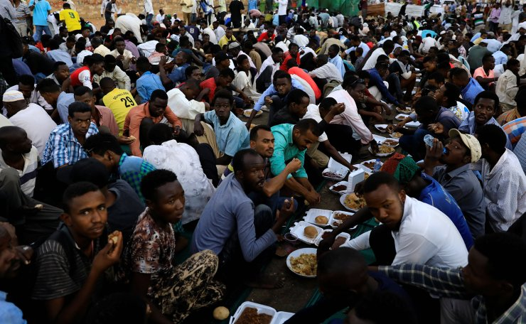 Sudanese protesters eat as they break their fast during the first day of the fasting month of Ramadan in front of the defense ministry compound in Khartoum, Sudan, May 6, 2019. Reuters