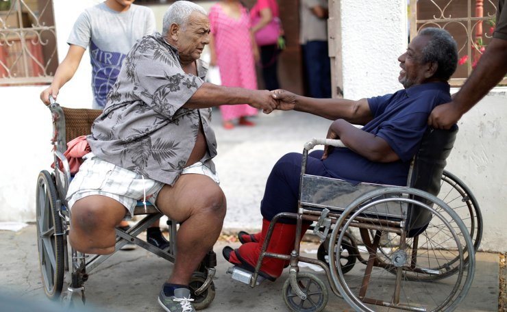 Elimenes Fuenmayor, 65, a patient with kidney disease, greets another kidney disease patient, as they wait for the electricity to return during a blackout, in front of a dialysis centre, in Maracaibo, Venezuela April 11, 2019. Reuters