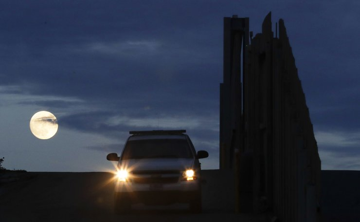The moon rises behind a United States Border Patrol vehicle as it sits near one of the border walls separating Tijuana, Mexico and San Diego Wednesday, Nov. 21, 2018, in San Diego. AP