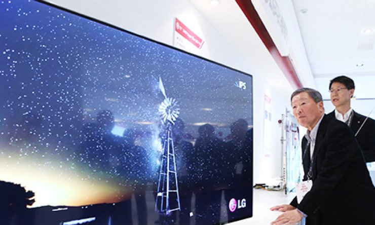 LG Chairman Koo Bon-moo checks out the thickness and viewing quality of a new LG Electronics TV that uses highly advanced display panels supplied by LG Display, during an internal event at LG Electronics' research center in Secho, southern Seoul, Thursday. / Courtesy of LG