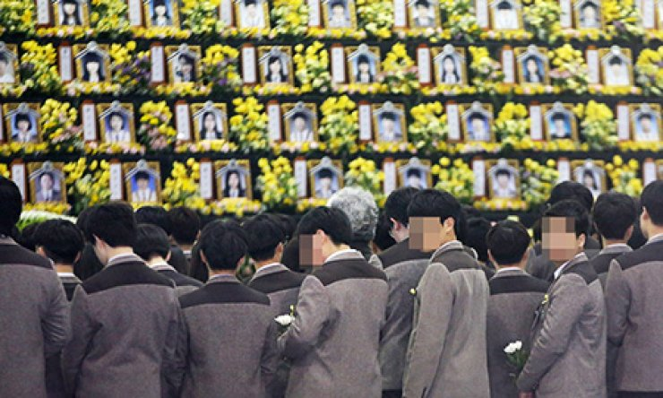 Danwon High School students pay tribute to the victims of the ferry Sewol tragedy at a memorial altar at the school in Ansan, Gyeonggi Province, Thursday, on the first anniversary of the disaster. / Yonhap