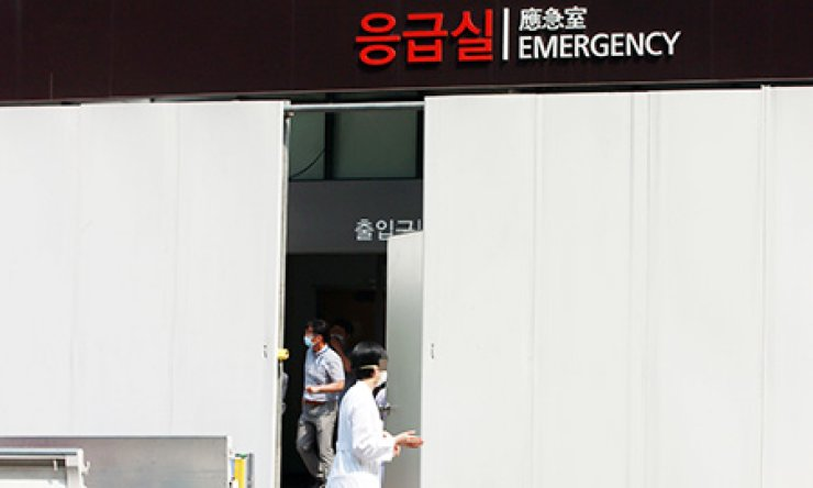 A medical staffer at Samsung Medical Center passes through a door of a temporary fence erected in front of the emergency room, which was closed due to a large outbreak of Middle East Respiratory Syndrome there, Monday. / Yonhap