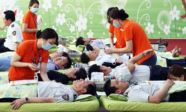 Police officers donate blood at the Korean National Police Agency in central Seoul, Monday. Hospitals are suffering from a shortage of blood as people avoid visiting blood donation centers out of fears of possible infection with Middle East Respiratory Syndrome. / Yonhap
