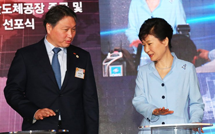 President Park Geun-hye talks with SK Group Chairman Chey Tae-won during a ceremony Tuesday to mark SK hynix's latest chip manufacturing line - M14 - in Icheon, Gyeonggi Province, where the headquarters of SK hynix are located./ Yonhap