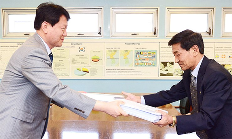 Red Cross officials from South and North Korea exchange lists of candidates for family reunions at the truce village of Panmunjeom, Tuesday. The officials will check whether the people on the lists are still alive and available for reunions scheduled to run from Oct. 20 to 26 at Mount Geumgang in the North. / Courtesy of the Ministry of Unification