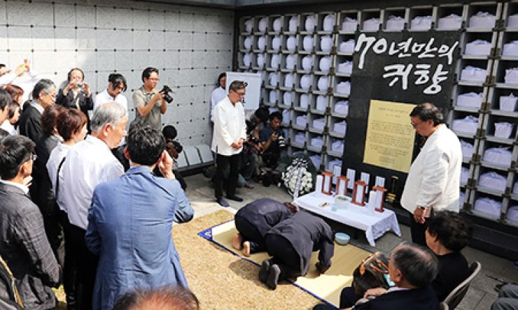 Activists bow before the remains of 115 Koreans who died after being taken to Japan and forced into slave labor during the 1940s during a memorial ceremony to mark their posthumous repatriation into a cemetery in Yongin, Gyeonggi Province, Sunday. / Yonhap