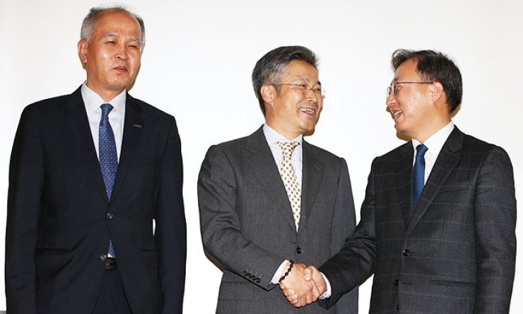 Daniel Yun, right, head of Kakao's mobile bank taskforce, shakes hands with Kim In-hoe, center, executive vice president at KT's K-Bank operating committee, before a press conference at the Korea Federation of Banks, in Myeongdong, central Seoul, Monday. / Yonhap