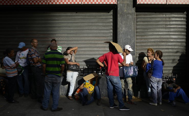 People wait to shop at a supermarket in Chacao neighborhood where the Venezuelan cryptocurrency, Petro, is accepted in Caracas, Venezuela, Monday, Dec. 30, 2019. AP