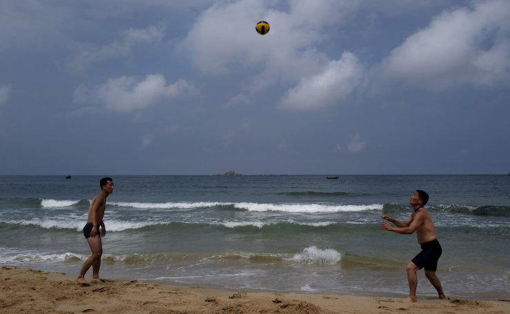In this Sunday, July 14, 2019, photo, two man play with volleyball at Sijung Ho beach in North Korea. The beach is a popular tourist destination for locals and foreigners alike. AP