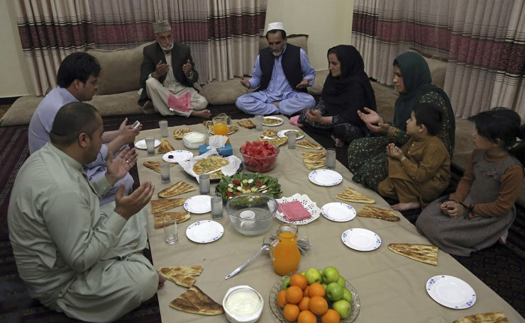 An Afghan family pray as they prepare to break their fast with the Iftar meal at sundown, on the first day of the holy month of Ramadan, in Kabul, Afghanistan, Monday, May 6, 2019. AP