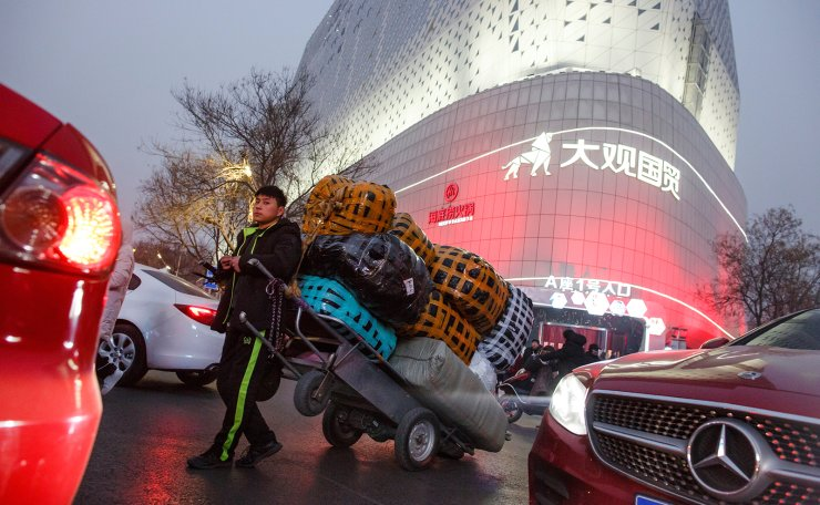 A deliveryman leans against a cart outside a wholesale market in central Zhengzhou, Henan province, China January 19, 2019. Reuters