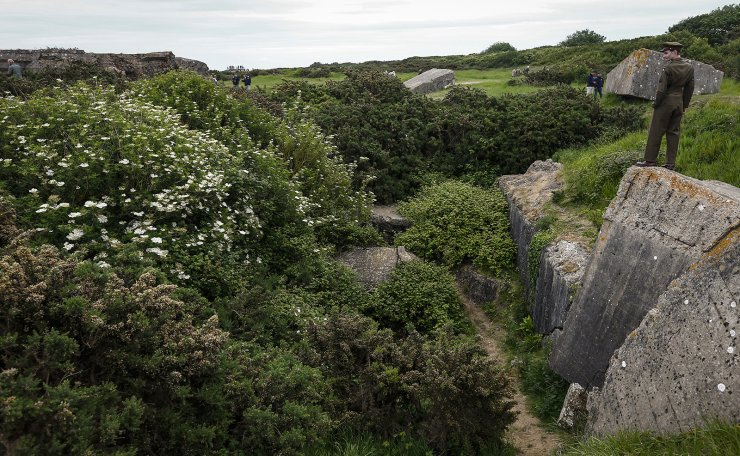 History enthusiasts in uniform look over the ruins of a German bunker, near the Normandy coast ahead of the 75th D-Day anniversary, in Pointe Du Hoc  France, 04 June 2019. EPA