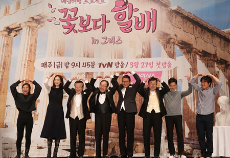 The cast members of the reality show 'Grandpas Over Flowers' make heart shapes over their heads during a press conference at 63 Square in Seoul, last Tuesday. From left are producer Park Hee-yeon, actress Choi Ji-woo, actors Lee Soon-jae, Shin Goo, Park Geun-hyung, Baek Il-seob and Lee Seo-jin, and producer Na Young-seok. / Yonhap