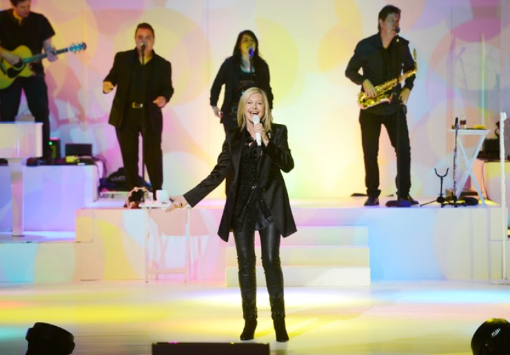 Olivia Newton-John performs with her band members in April 2014. / Courtesy of World Show Market