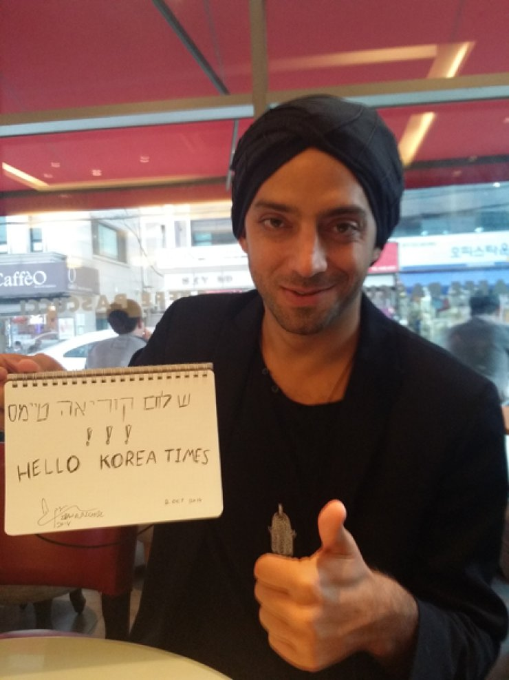 Israeli singer-songwriter Idan Raichel holds his autograph for The Korea Times readers during an interview Thursday./ Korea Times photo by Kim Hye-kyung