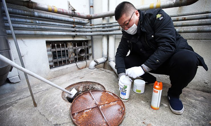 A health official puts a chemical to eradicate mosquito larvae in a sewer in Yongsan, Seoul, Monday, amid growing fear over the mosquito-borne Zika virus. The virus is linked to the birth defect microcephaly, spreading rapidly in the Americas. / Yonhap