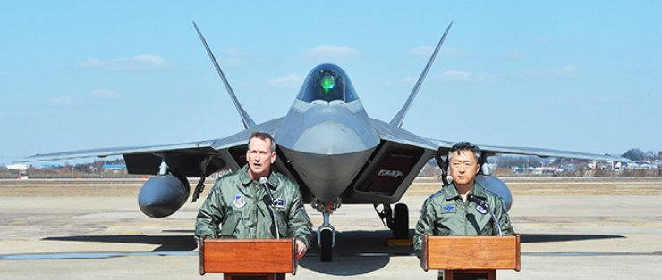 Lt. Gen. Terrence J. O'Shaughnessy, left, commander of U.S. Seventh Air Force and deputy commander of U.S. Forces Korea, announces a joint statement with ROK Air Force Operations Command Commander Lt. Gen. Lee Wang-keon in front of an F-22 Raptor stealth fighter at Osan Air Base in Pyeongtaek, Gyeonggi Province, Wednesday. Four F-22s performed a flyover to demonstrate the power of the Seoul-Washington alliance. O'Shaughnessy said the U.S. maintains an ironclad commitment to the defense of the Republic of Korea. / Joint press corps