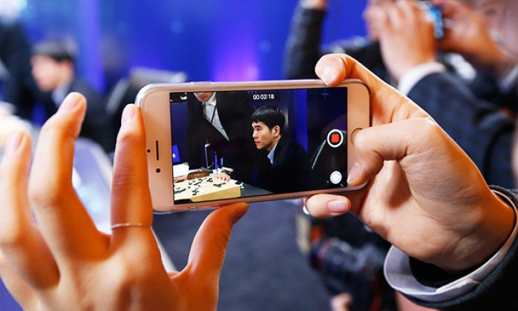 A woman films professional Go player Lee Se-dol after winning the fourth game of the Google DeepMind Challenge Match against Google's artificial intelligence program, Alpha-Go, in Seoul, Sunday. / AP-Yonhap