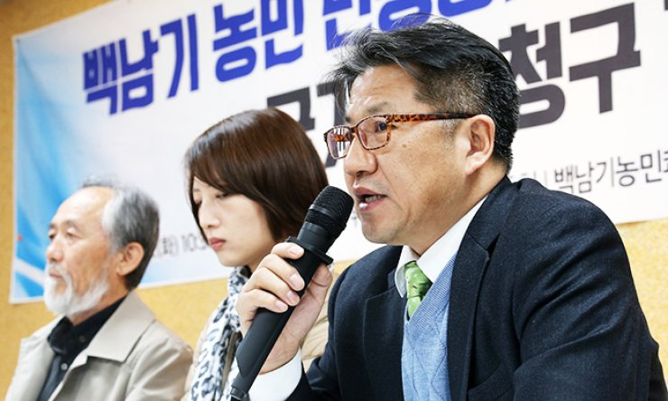Lawyers for a Democratic Society Secretary General Cho Young-sun, right, speaks at a press conference in Seoul, Tuesday, about a damages suit against the government and police by the family of Baek Nam-ki, a farmer who has been in a coma after being hit by a police water cannon at an anti-government rally last year. / Yonhap