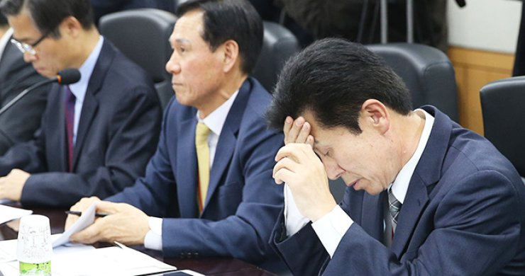 Hanjin Newport Corp. CEO Jung Se-hwa, right, touches his forehead at an emergency meeting regarding the restructuring of the shipping industry held at the Ministry of Oceans and Fisheries in Sejong City, Monday. / Yonhap