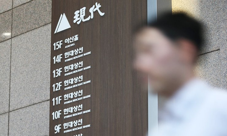 An employee of Hyundai Merchant Marine (HMM) passes by the shipper's main office in downtown Seoul, Wednesday. HMM failed to reach a deal with foreign containership owners to cut their charter fees. / Yonhap