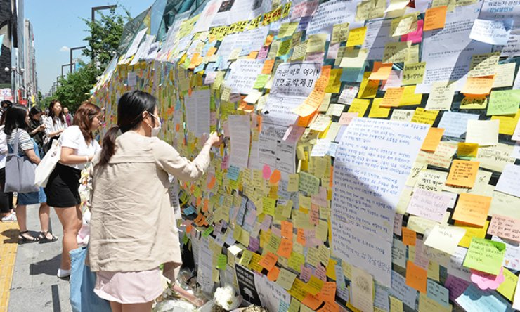 The wall at exit 10 of Gangnam Station in southern Seoul is covered with memos and flowers left there by citizens, Thursday, in memory of a woman who was murdered in a nearby building, Tuesday. / Korea Times photo by Shin Sang-soon