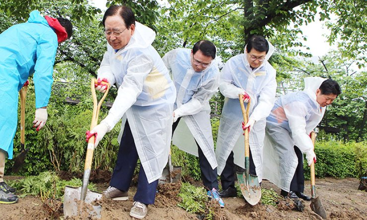 Shinhan Financial Group Chairman Han Dong-woo, second from left, digs a hole to plant a tree with chief executives of the group on May 10. They are making a playground designed to be wheelchair accessible at Children's Grand Park in eastern Seoul. / Courtesy of Shinhan Financial Group