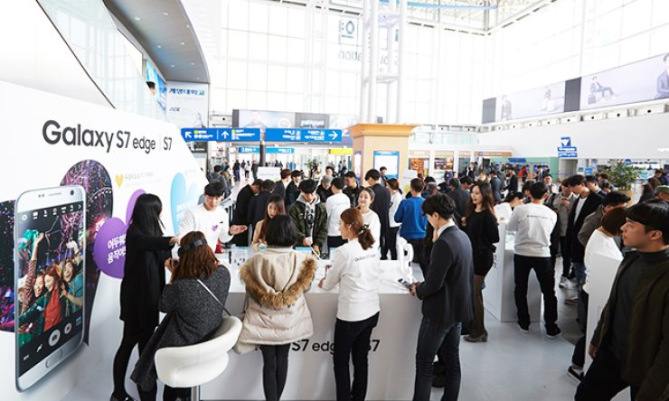Consumers check features of the Samsung Galaxy S7 and S7 Edge at the Galaxy S7 Experience Zone installed in Seoul Station in this file photo. / Korea Times file