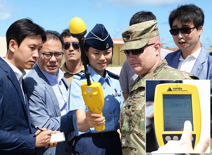 A South Korean officer, second from right, measures electromagnetic waves emitted from the AN/TPY-2 radar of the Terminal High Altitude Area Defense (THAAD) system at Andersen Air Force Base in Guam, Monday, while South Korean journalists and a U.S. officer look on. The inset photo shows the levels of the electromagnetic waves at 0.001 watts per square meter, which is much lower than the 10 watts per square meter permissible level in daily life set by the Korea Communications Commission. / Courtesy of U.S. Air Force