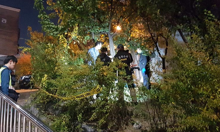 Policemen examine the shooting scene in Beon-dong, northeastern Seoul, Wednesday evening, after a criminal suspect shot a police officer. Investigators said the suspect, Seong, 46, fired at the officer after quarreling with his neighbor. The officer was pronounced dead after being taken to a nearby hospital. / Yonhap