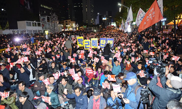 Protestors hold pickets which read 'Park Geun-hye resign' during a candlelight vigil on Saturday evening at Cheonggye Plaza, central Seoul. Almost 20,000 participants walked toward Cheong Wa Dae. / Korea Times photo by Shin Sang-soon