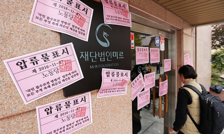 Stickers claiming property confiscation, placed in protest by members of the minor opposition Labor Party, are seen at the entrance of the Mir Foundation building in southern Seoul, Monday. Opposition parties seek to set up a special act to confiscate assets illegally accumulated by President Park Geun-hye's scandal-ridden confidant Choi Soon-sil. The foundation was allegedly set up and controlled by Choi for personal gain. / Yonhap