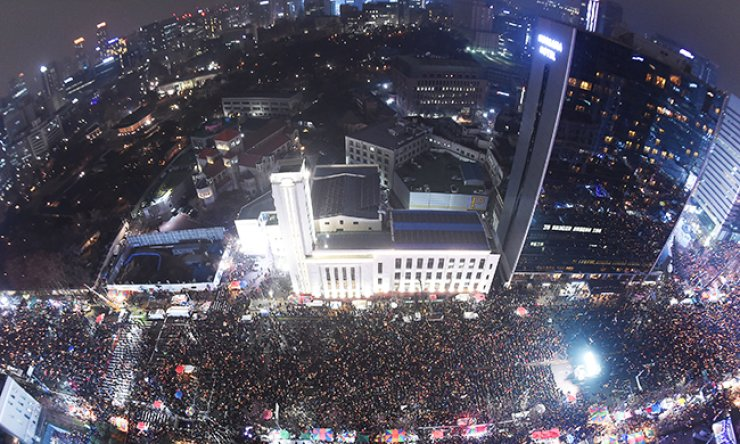Protesters hold up candles calling for the resignation of President Park Geun-hye, who allegedly helped her longtime friend Choi Soon-sil meddle in state affairs, as police officers stand in front of them at Gwanghwamun Square in central Seoul, Saturday. / Yonhap
